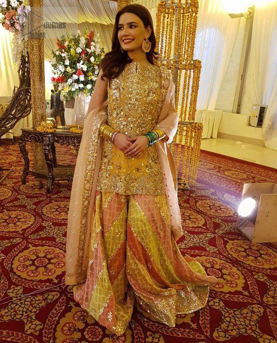 Amber shirt adorned with mainly light golden embellishment on neckline, hemline and side slits.  Pink peach dupatta adorned with embellished border and stripes.
