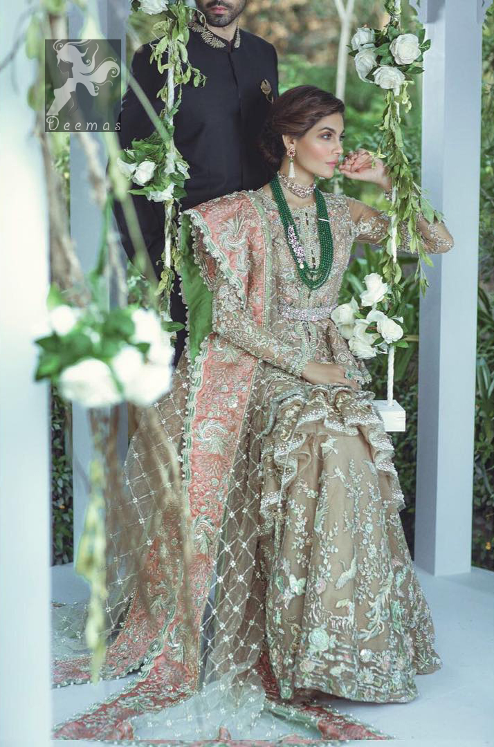 Fawn short length peplum made with net having embellished belt on waist. Large embellished border having peach appliqued on dupatta. Dupatta is adorned with rectangular shapes of embellishment small motifs all over it. Fitted lehenga having extra layer above the knees.
