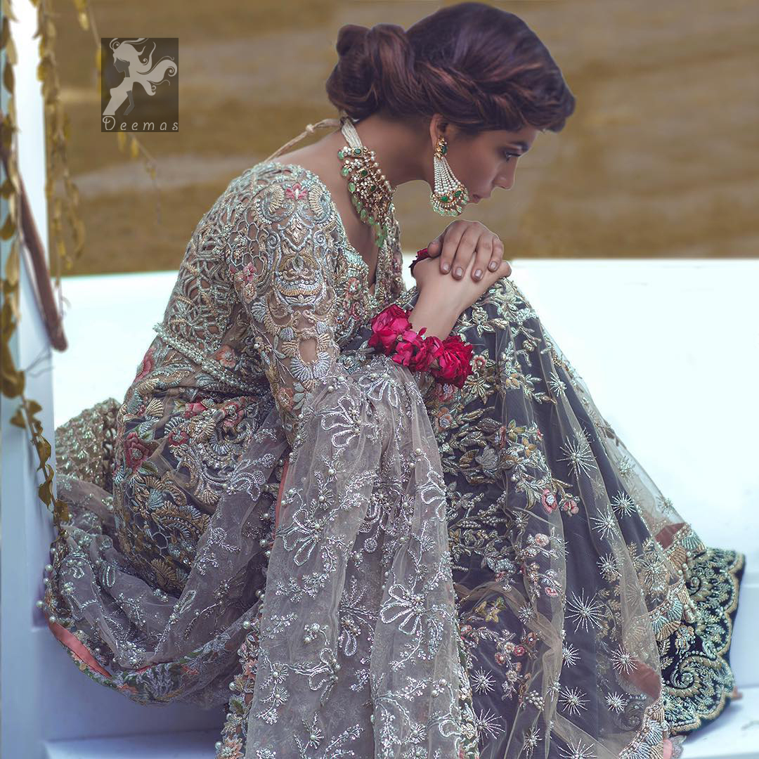 Light grayish fawn net maxi and dupatta. Bridal maxi adorned with silver, light golden, antique shades and colorful thread embellishment. Light grayish fawn net dupatta adorned with embellished border and large motifs all over it. Blackcurrant velvet sharara adorned with silver and light golden embellished border.