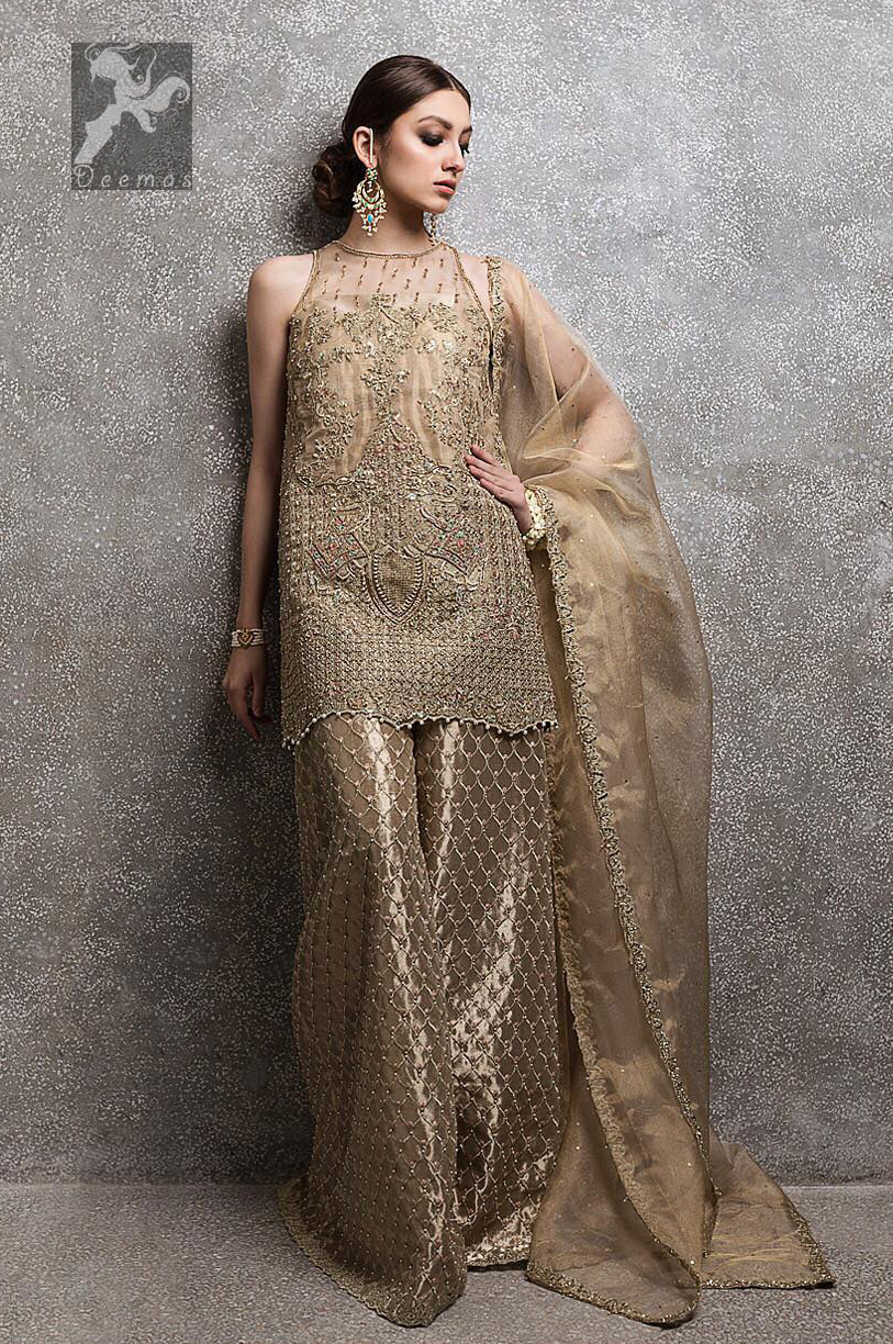 Light golden brown pure organza short shirt having halterneck design. Shirt has been embellished with antique and different shades of embellishment. Small embellishment border on dupatta. Sharara is adorned with embellishment all over it.