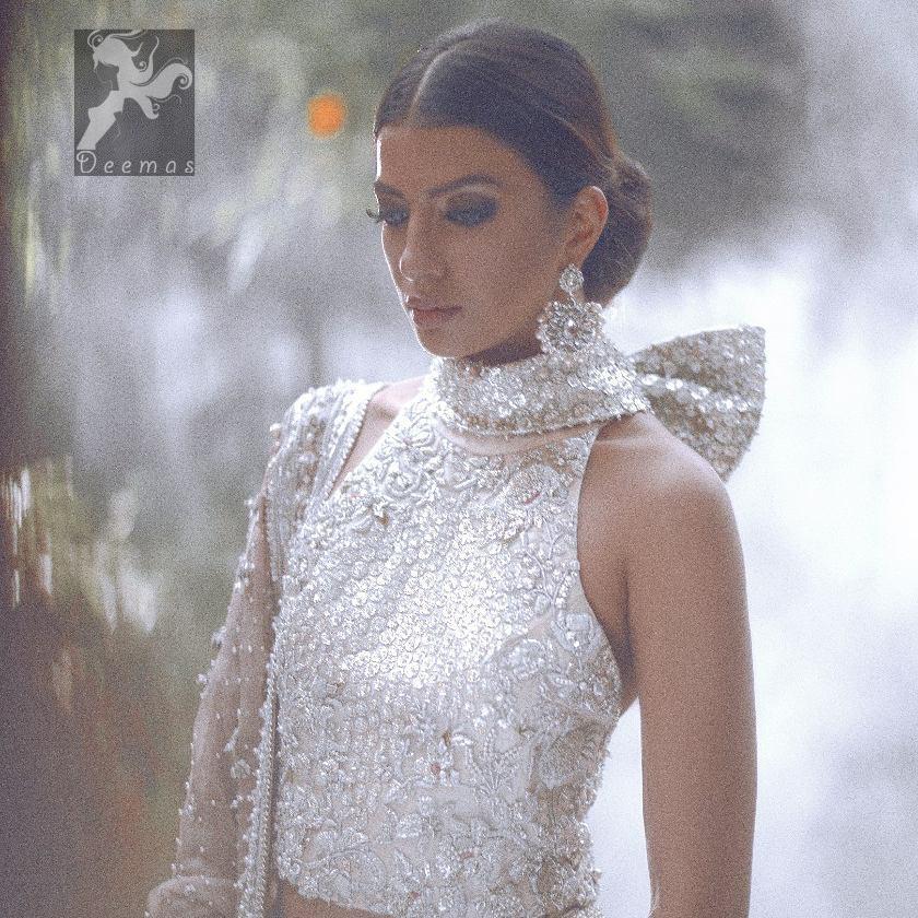 White choli / blouse having beautiful embellishment in white, silver and maroon brown. Halterneck design has been implemented on blouse / choli. White lehenga / skirt having heavy embellishment.