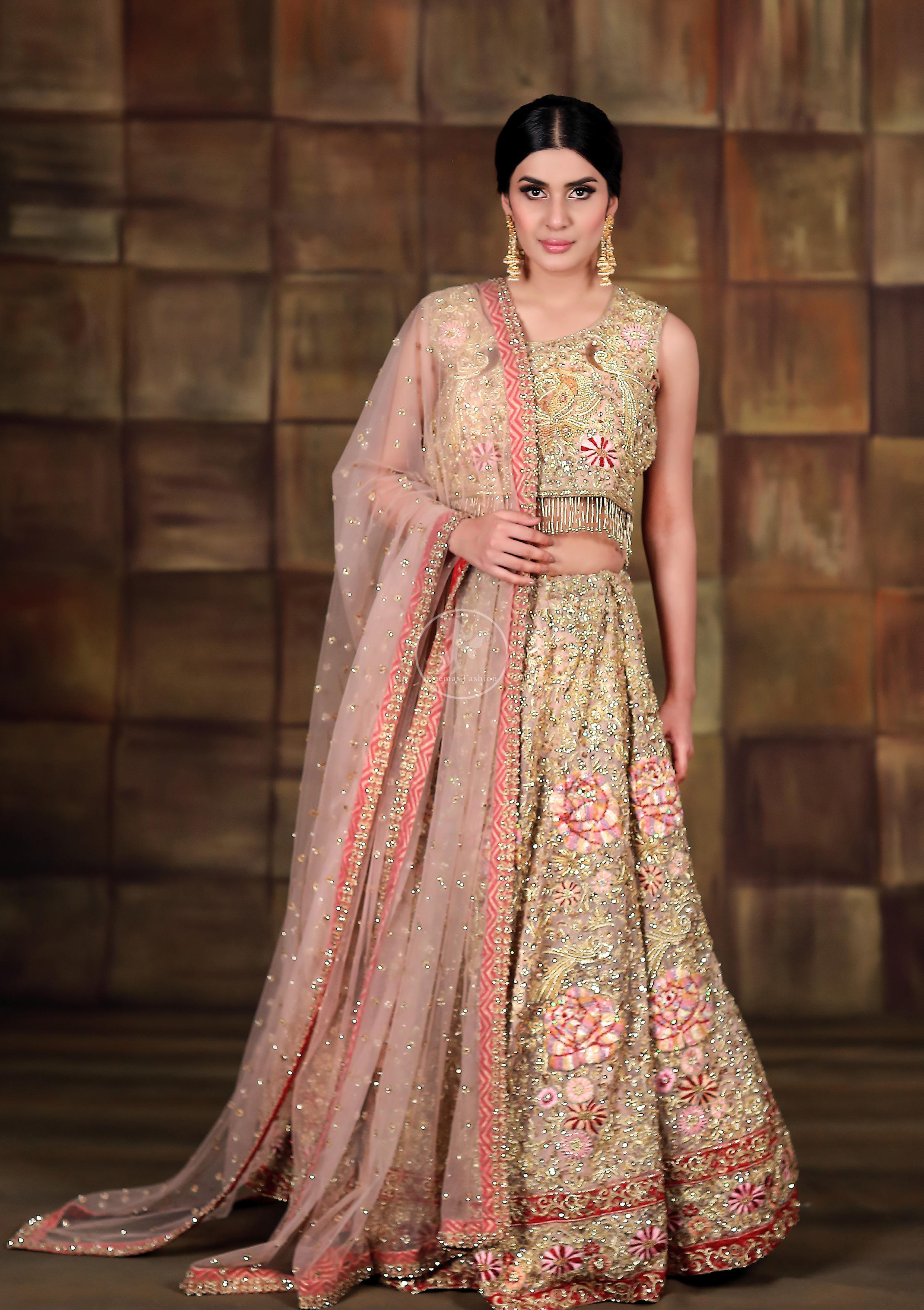 This dress is beautifully sculptured with floral thread embroidery. Blouse is fully embellished and decorated with tassels. Lehengha is embellished with different shaded thread embroidery, allured with kora, dabka, tilla, sequins and pearls. It comes with net dupatta which has four sided embroidered border and sprinkled with pearls and sequins all over it.