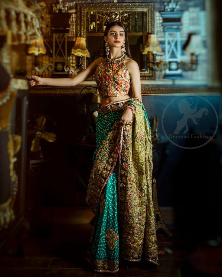 This outfit is a timeless beauty. It is heavily embellished with antique gold kora, dabka, tilla, sequins and swarovski crystals. This exquisite halter neckline blouse is fully decorated with floral motifs patterns all over it. Applique waist belt is decorated with gota and thread embroidery.It comes with embellished lehengha. This Outfit is beautifully coordinated with lime yellow dupatta with heavy embroidered borders.