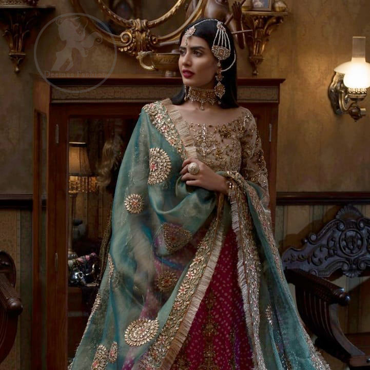 This outfit is a timeless beauty. Its blouse is heavily embellished with silver gold kora, dabka, sequins and swaronski crystals. This exquisite blouse is fully decorated with floral motifs patterns all over it. Boat shaped neckline add to the look. It comes with shocking pink chunri lehenga which has small sized sprinkled floral motifs all over. This outfit is beautifully coordinated with organza dupatta. Dupatta is embellished with kiran lace and gotta work on sides.