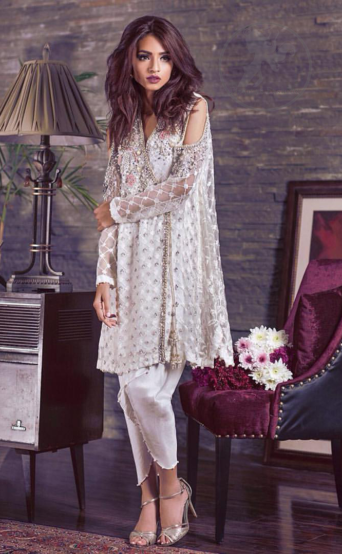 This beautiful angrakha style shirt adorned with embroidered featuring silver and antique shaded kora dabka, tilla, sequins and swarowski. Hemline is decorated with pearls. There is cold shoulder design on sleeves which adds to the look. It comes with brocade pajama.It is coordinated with net dupatta having sprinkled sequins all over it.