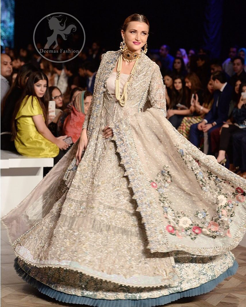 This outfit is a timeless beauty. It is heavily embellished with silver gold kora dabka, Sequins and swarovski crystals. This exquisite Pishwas is fully decorated with floral motifs patterns all over it. It is further enhanced with multiple colored Foral thread embroidery. The applique border of pishwas is ornamented with small silver pearls. It comes with embellished lehenga which has small sized sprinkled floral motifs all over. This Outfit is beautifully coordinated with matching Dupatta with heavy embroidered borders.