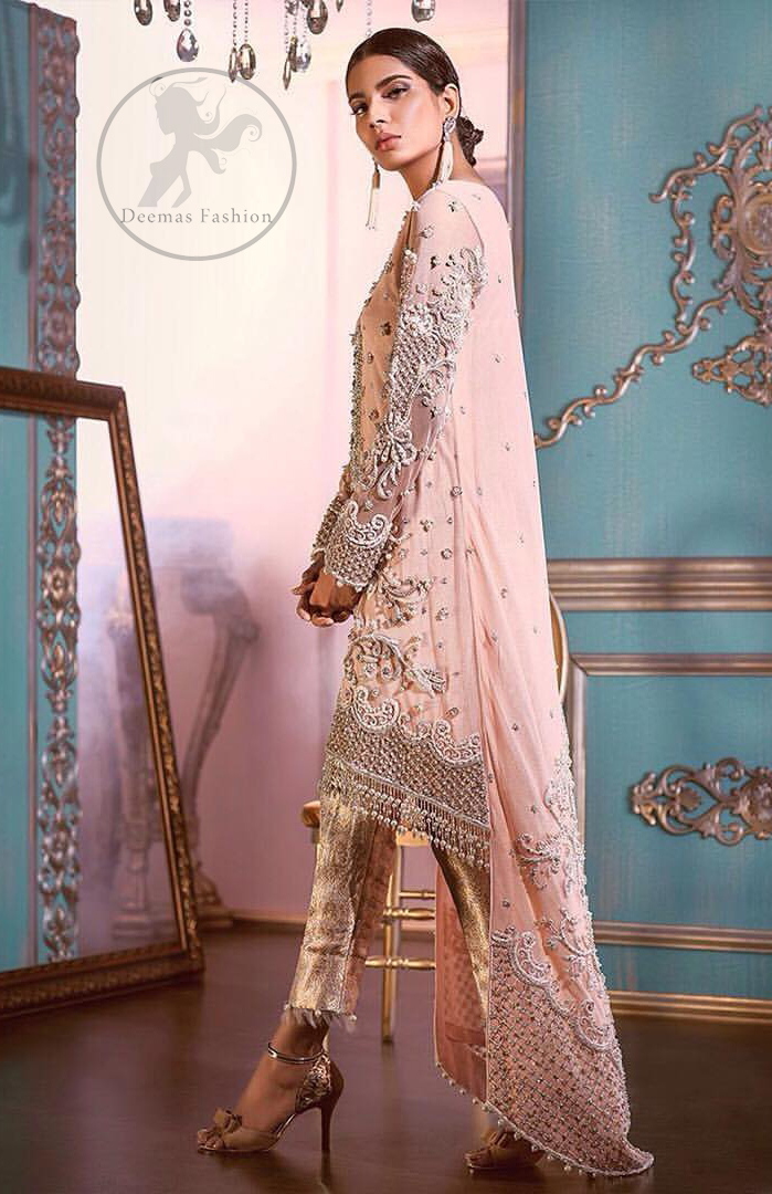 This outfit is decorated with silver kora, dabka, tilla, sequins and pearls. This dress is embellished with floral embroidery and intricate embroidered hemline. It is adorned with beautiful tassels which adds to the look. Sleeves are fully embellished. Trail is also embellished. It comes with brocade pajama. It is coordinated with chiffon dupatta which is sprinkled with sequins all over it.