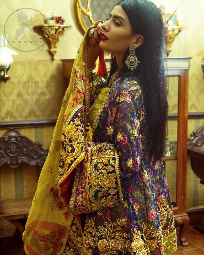 This royal blue angrakha shirt is embellished with resham thread. It is meticulously highlighted with dull golden kora dabka, tilla, sequins and pearls. Sleeves and neckline are adorned with gotta work as well. Hemline is allured with embroidered applique. It comes with embellished gharara which has sprinkled floral motifs. This Outfit is beautifully coordinated with yellow dupatta with heavy embroidered borders.