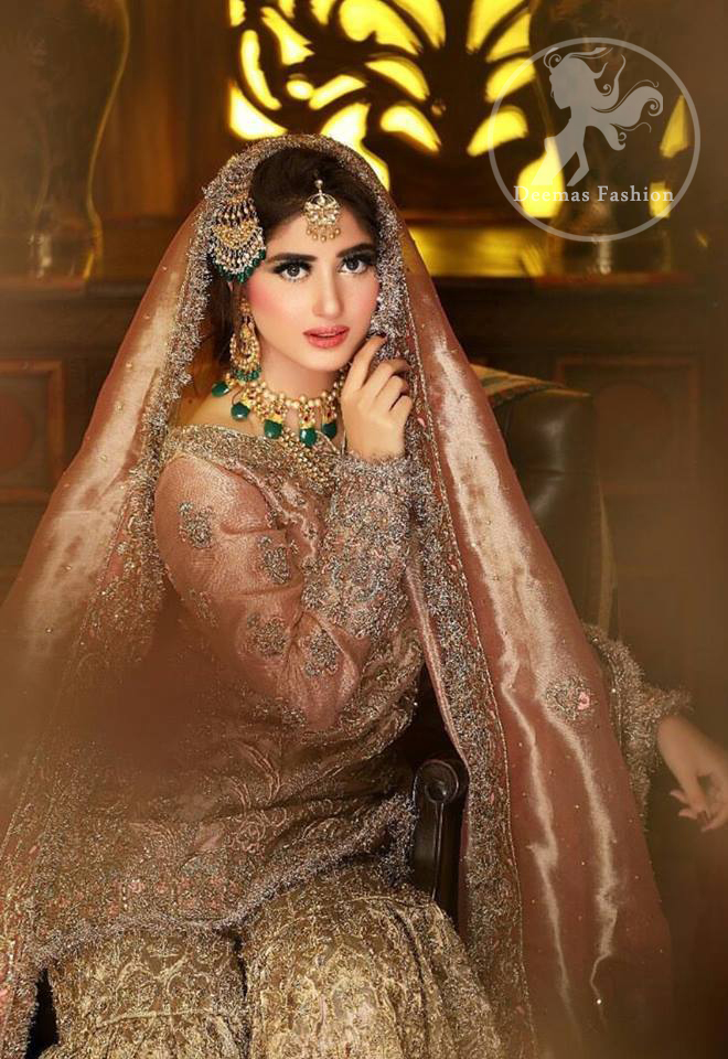 Feel glamorous in antique brass short shirt with fascinating embellishment on neckline with golden kora dabka, tilla and pearls. Floral motifs on sleeves add to the look. It is stunningly coordinated with traditional golden gharara. Complete the look with tilla work organza dupatta finessed with embroidered borders.