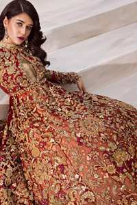 The grand maroon bridal stands out due to its uniqueness and the perfect fusion of modern cut and traditional embroidery. This halter neckline maxi is done with heavy embellishment of golden kora dabka, kundan, tilla, pearls and sequins work. It is further ornamented with detailed floral motifs. It is coordinated with brocade churidar pajama.