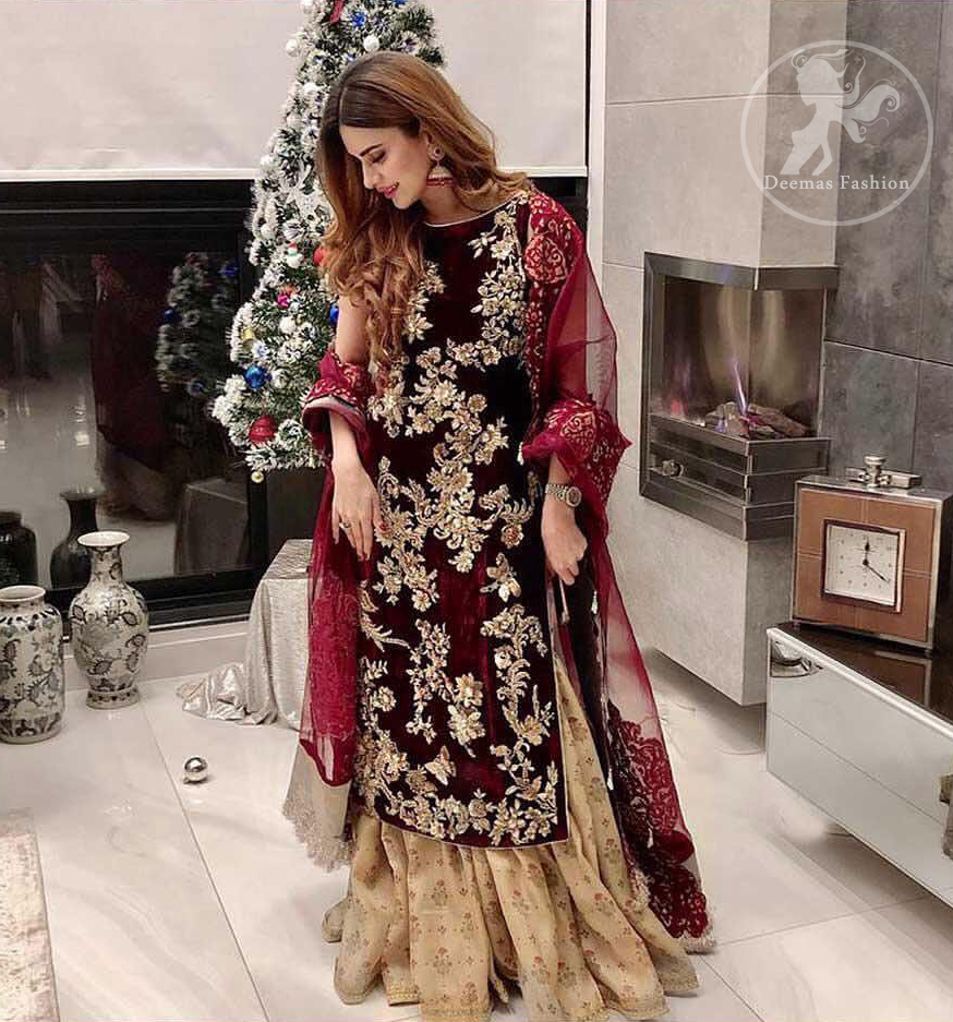 Take a step towards refreshing your wardrobe with maroon velvet dress. This maroon shirt is heavily embellished in the front with silver gold kora dabka, kundan, tilla and sequins. Finished with golden brocade self-printed gharara. This outfit is beautifully coordinates with maroon dupatta with embroidered borders on all four sides .