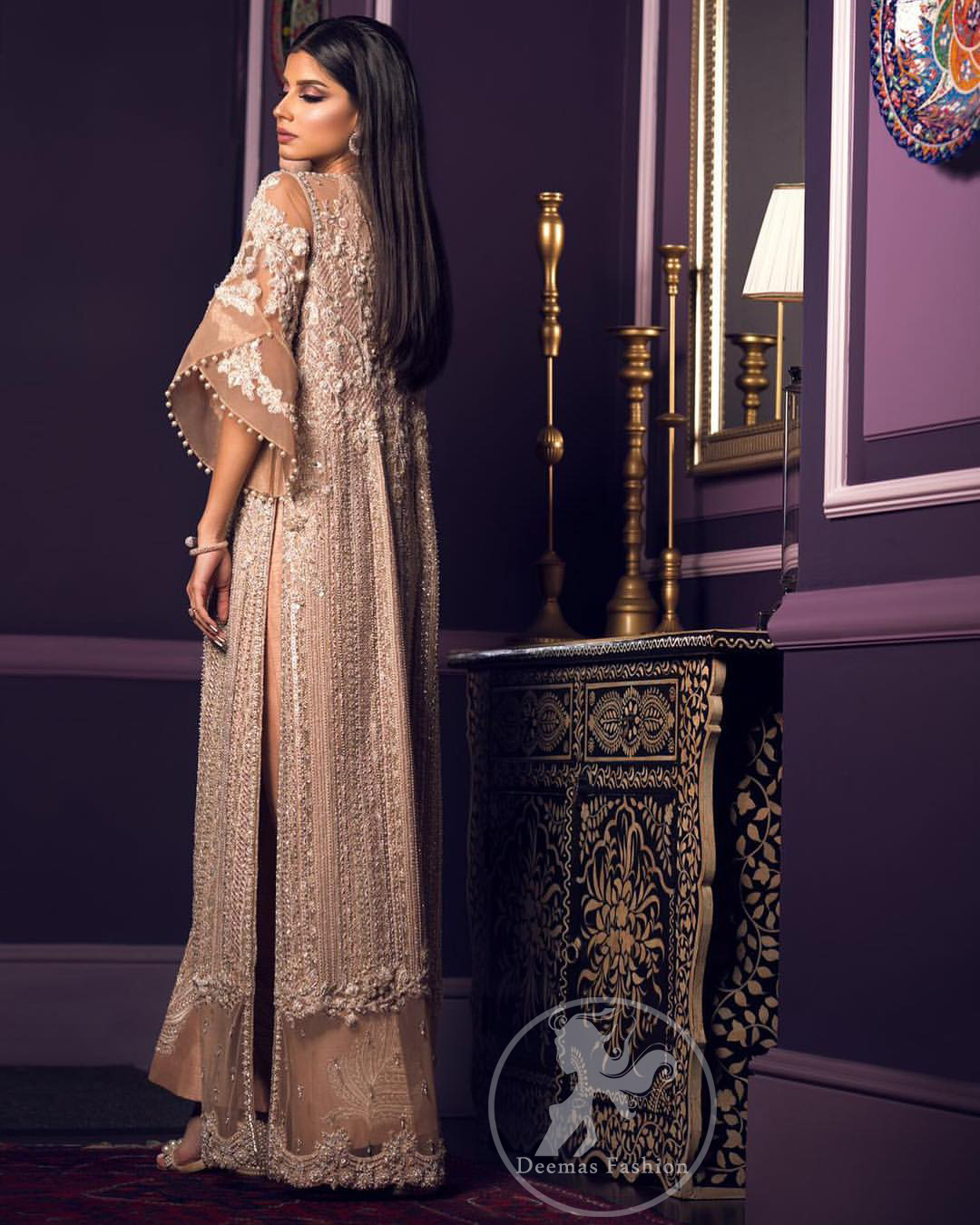 This dress is decorated with floral embroidery. It is highlighted with kora, dabka, tilla, sequins and pearls. Gown is adorned with scalloped border and tassels which adds to the look. It comes with trousers. It is coordinated with organza dupatta which is sprinkled with sequins all over it.