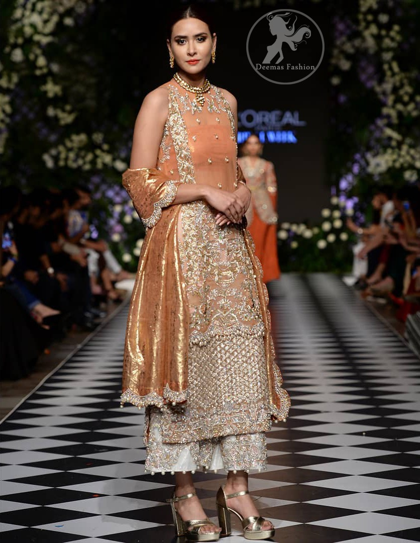This outfit is stunningly perfect for any evening ensemble. It is paired with a sleeveless double layered shirt in organza fabric which is extensively hand worked in crystals and zardozi. This dress is beautifully sculptured with dull golden floral embroidery, adorned with cutwork borders embellished with tassels, kora, dabka, pearl and sequins work all over. It comes with embroidered trousers. It is coordinated with tissue dupatta which is furnished with four sided scalloped border.