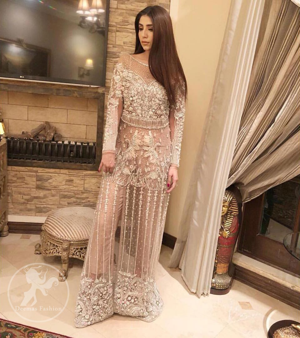 Exude elegance and class in this shirt finessed with beautiful embellished daaman. This dress is beautifully decorated with heavy embroidery. It is highlighted with silver kora, dabka, tilla, sequins and pearls. Bodice is ornamented with heavy embellishment and addition of tassels to complete the look. It comes with matching capri. It is coordinated with chiffon dupatta which is sprinkled with sequins all over it.
