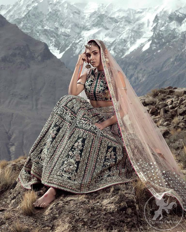 This dress is beautifully decorated with heavy embroidery. It is highlighted with dull golden kora, dabka, tilla, sequins and pearls. Fish lehengha is fully embellished.Blouse is scalloped. It comes with beautifull upper gown, sprinkled with sequins all over it. It is coordinated with chiffon dupatta which is sprinkled with sequins all over it.