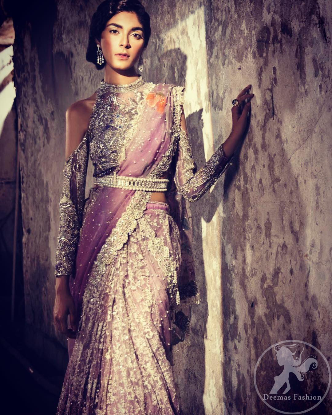 This dress is beautifully sculptured with floral embroidery. It comes with fully embroidered brocade blouse having halter neckline which adds to the look. Pallu is highlighted with kora, dabka, tilla, sequins and pearls. It is allured with scalloped embroidered border. Lehengha is fully embellished.