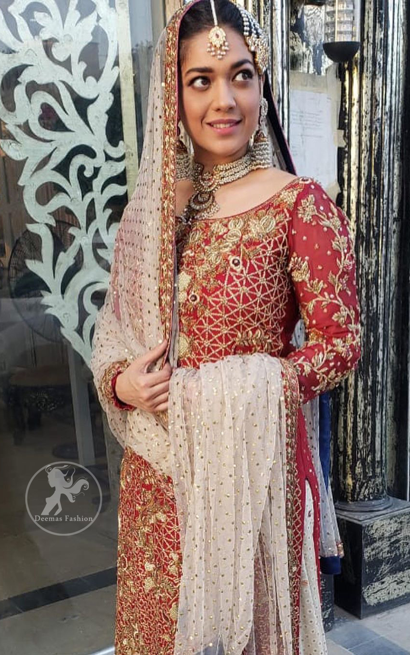 Make a dazzling impression in our zari embroidered copper rust shirt enhanced with intricately embellishmentswith gold and antique gold kora, dabka, tilla, sequins and pearls.It is paired up with thread embroidered chiffon lehengha having appliqued border around. Dupatta is sprinkled with stones all over it.