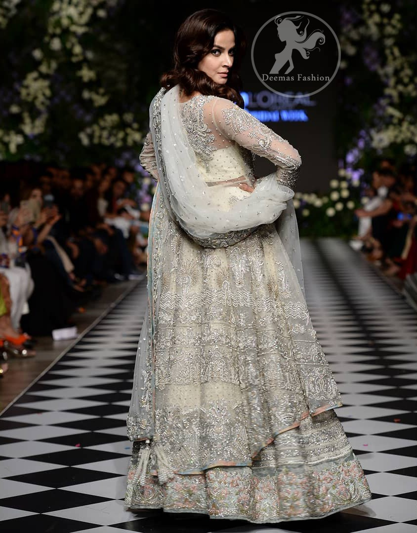 Feel glamorous in our ivory back trail frock with fascinating embellishment on neckline with silver kora, dabka, pearl and sequins. The detailed embellishment at the daaman instantly draws attention. It comes with an exquisite lehenga with thick embroidered borders to give it a regal look. The outfit is finished by beautiful applique embellished lehenga. It is coordinated with tissue dupatta which is sprinkled with sequins all over it. It is further furnished with four sided embellished border.