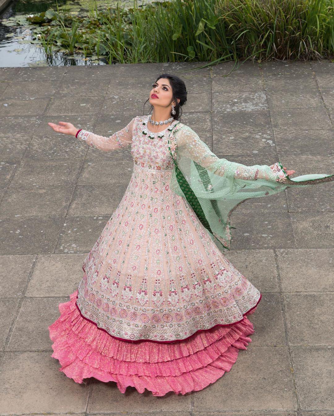 Opt for our ivory multiple-panel anarkali dress with exquisite embellishment on the bodice with pearls, sequins and silver kora, dabka. The daaman comprises of borders highlighted with floral embellished pattern. It is finished with deep blush frilled lehengha which adds to the bling. Dupatta is allured with four sided embellished border and sprinkled with stones all over it.