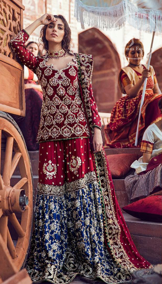 A beautiful short shirt heavily embellished with silver work enhanced with kora, dabka, tilla, sequins and stones. It is artistically coordinated with blue jamawar farshi gharara with floral embellished pattern at the bottom and finished with an appliqued embellished border. It is beautifully coordinated with jamawar dupatta sprinkled with small motifs andan appliqued border finished around dupatta.