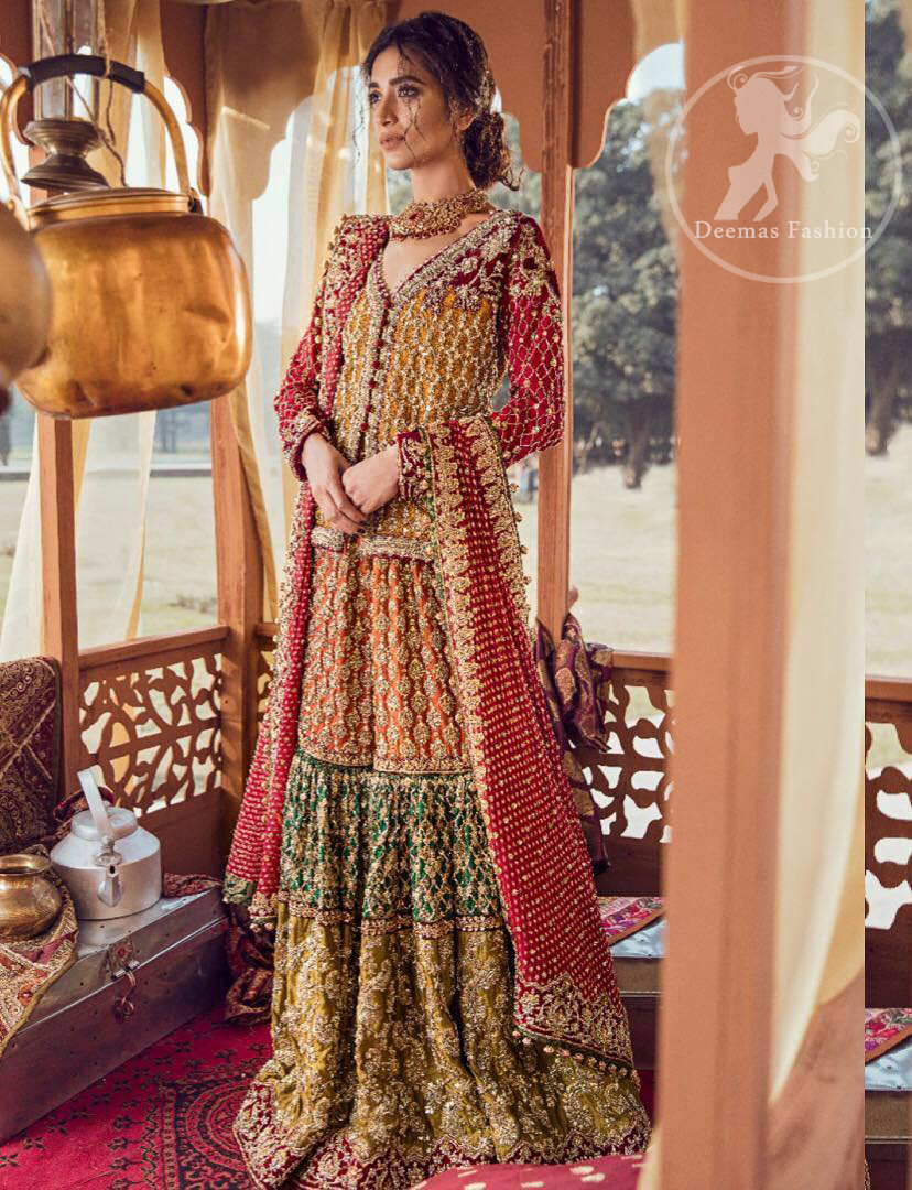 Exquisite detailing radiates elegance in this stunning short shirt. Redefine your style in this traditional and versatile ensemble ornamented with floral and geometric embroidery furnished with golden kora dabka, kundan and pearls. It comes with multiple colored traditional gharara done with zerdozi work in patterns and embroidered applique details on bottom. Complete the look with red dupatta having embroidered borders on all sides and sequins spray on the ground.