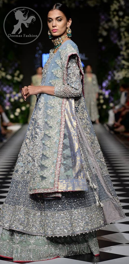 Boost your confidence and style in this glamorous attire accentuated with finest zardosi work embroidery and cut work neckline. It is beautifully decorated with heavy embroidery. It is highlighted with silver kora, dabka, tilla, sequins and pearls. It comes with heavily embroidered lehenga which is decorated with red piping from the bottom. It is coordinated with tissue dupatta which is sprinkled with sequins all over it. It is further furnished with four sided embellished border.