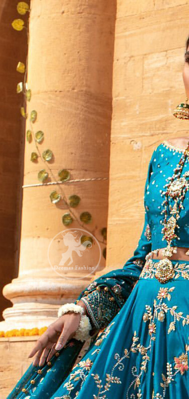 Feel glamorous in our venice blue blouse skirt with fascinating embellishment on neckline with silver kora dabka, pearl and sequins. The bridal stands out due to its uniqueness and the perfect fusion of modern cut and traditional embroidery. Blouse has simply sprinkled with perals and lehenga has embroidered applique on bottom and embellished waist belt. It is coordinated with tissue dupatta which is sprinkled with sequins all over it. It is further furnished with four sided embellished border.