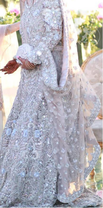 The grand gold bridal stands out due to its uniqueness and the perfect fusion of modern cut and traditional embroidery. This dress is beautifully decorated with heavy embroidery. It is highlighted with kora, dabka, tilla, sequins and pearls. Style it up with embellished wait belt. It comes with brocade pajama. It is coordinated with tissue dupatta which is sprinkled with sequins all over it. It is further furnished with four sided thick embellished border.