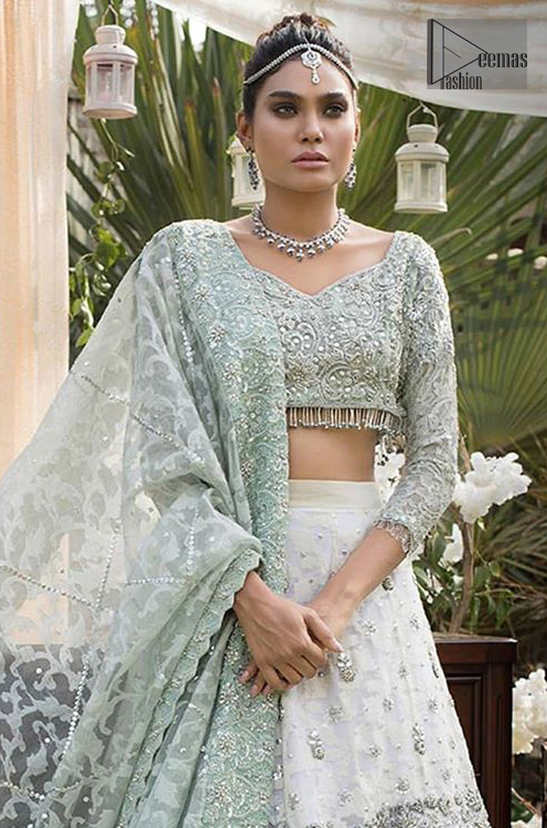 This bridal dress is perfect for your wedding or nikah day. Create a vision of elegance with this ivory self printed lehenga decorated with intricate zardosi detailing and silver kora, dabka and sequins. Furthermore it is adorned with scattered tiny floral motifs. Having quarter sleeves adorned with motifs. Beautifully coordinated with heavy embellished blouse with silver kora, dabka, sequins and pearls all over and finishing with tassels at the end. It comprises with light green self printed dupatta having matha patti border on the front and intricate beautiful border on all rest of the three sides.