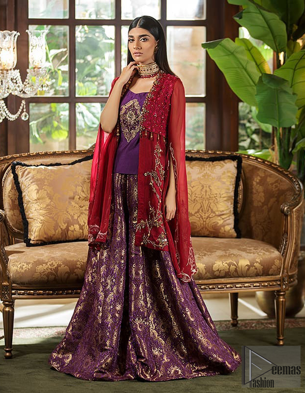 Tradition meets modernity. Boost your confidence and style in this glamorous attire accentuated with finest zardosi work, stunningly perfect for any evening ensemle. Short shirt is ornamented with a large motif in the center done with antique shaded kora, dabka, tilla and sequins. Pair it up with deep red gown beautifully adorned with floral thread embroidery on the bodice and finishing with tassels. Furthermore it is highlighted with floral bootis. Finish the look with brocade sharara. It is comprises with golden brocade dupatta having embellished red applique on all four sides.