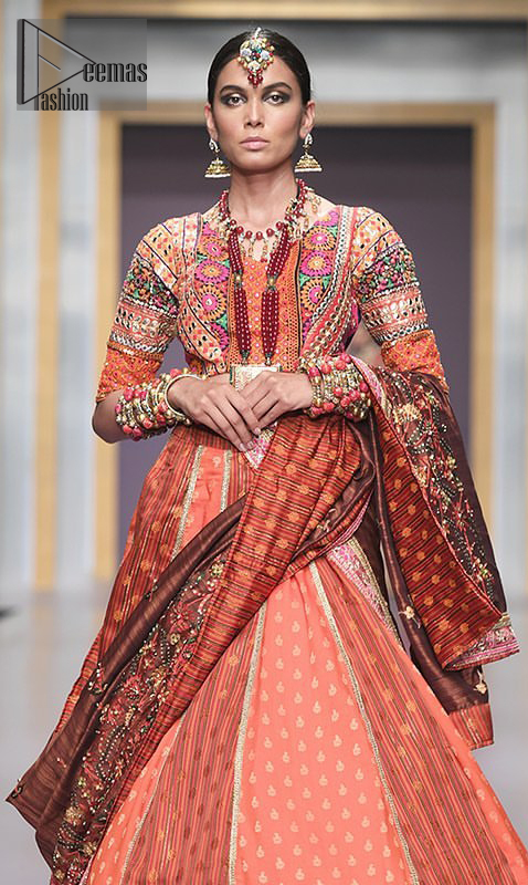 This dress is majestic beauty and perfect for mehndi mayon day. Delicately crafted and personifying chic elegance with an element of grandiose. A full heavily embellished blouse with multiple color resham thread embroidery and mirror work details. Having half sleeves adorned with mirror work. It comprises with self printed lehenga finishing with dull golden lace at the end. Style it confidently with chocolate brown dupatta with thick embellished border on the front and comparatively lighter work border on long edges. Medium and tiny sized ornamental motifs scattered all-over.