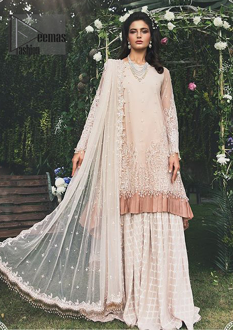Go for this trendy dress which is perfect for your nikah. Feel glamorous in our ivory a-line frock with fascinating embellishment on neckline with silver kora, dabka, pearl and sequins. The daman is emphasized with detailed matching embellishment and finished with choclate brown frill. It comprises with sharara adorned with criss cross pattern. This outfit is paired up with net dupatta focusing on kora and dabka handwork borders on all four sides, sequins spray all over and finished with tassels.