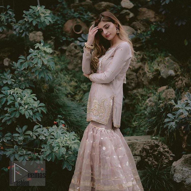 This dress is majestic beauty and perfect for your nikah or engagement day. Delicately crafted and personifying chic elegance with an element of grandiose. The beautiful neckline decorated with multiple color appliques, swarovski crystals and zardosi work. The daman is emphasized with golden kora, dabka,tilla and gota work to convey a classic look. Having full length sleeves adorned with tiny motifs scattered all over. This outfit is coordinated with self printed organza gharara. Pair it up with matching organza dupatta.
