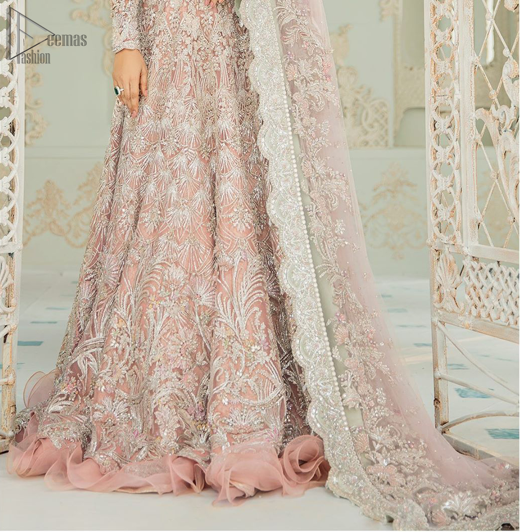 An example of beauty and elegance. Look breathtakingly stylish in this embroidered regalia furnished with intricate embroidered neckline. This ethereal maxi highlights the collision of heritage and beauty of traditional zardosi craftsmanship with modern chic silhouette. Beautifully designed sleeves is an amalgamation of geometric and floral design elements. The light pink net dupatta with chann and scalloped applique border all around the edges makes the look complete.