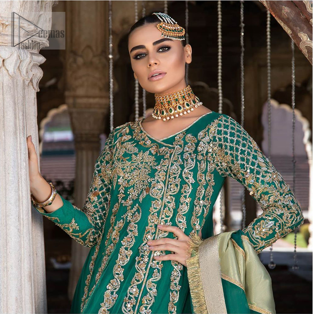 Steal the moment with our emerald green floor length angrakha emphasized with traditional neckline and intricate floral daman enhanced with light golden kora, dabka and sequins. The detailed zardosi work on sleeves and vertical panel stripes ornamented with gold kora and dabka embroidery on the bodice, the thick borders and floral bunches refined the classical royal look. Style it up with organza dupatta adorned with four sided kiran.