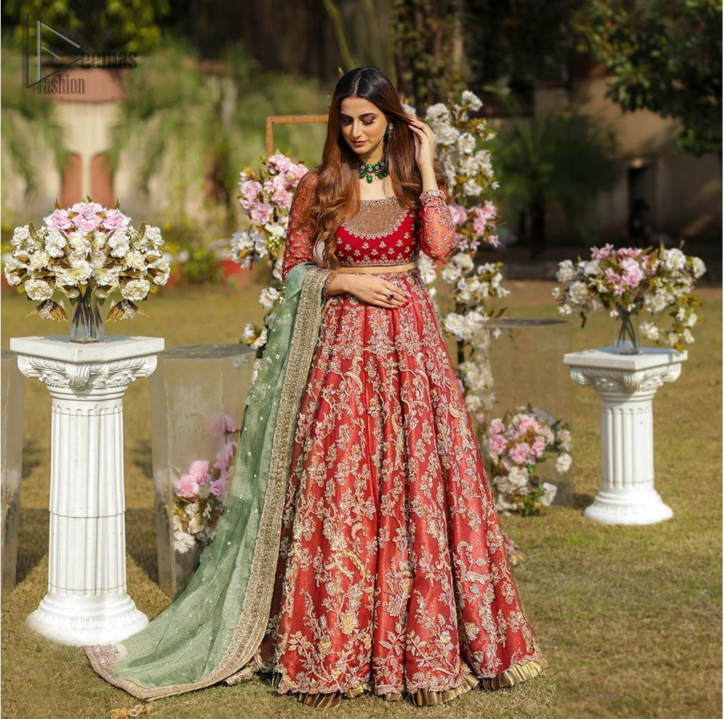 Make a special day even more magic with our exquisite bridal dress. This wedding dress is elegant and eye-catching in equal measure. Strike a breathtakingly elegant pose in this wedding dress, designed with a beautiful neckline embellished with sequins details and scattered tiny floral motifs all over. The lehenga is decorated with floral embroidery all over and finished with frilled fabric. The mint green organza dupatta with chann and finishing all around the edges makes the look complete.