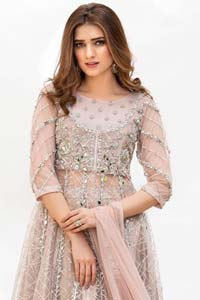 Embrace the season of festivities with this beautiful dress. Dazzle in this made to perfection, richly embroidered net outfit decorated with intricate embroidered front highlighted with silver and light golden zardozi work borders on daaman and embroidered stripes on sleeves. The bodice is fully furnished with zardozi work and sprinkled with floral motifs around neckline. The outfit is comprises with brocade sharara and tea pink net dupatta adorned with sequins spray all over.