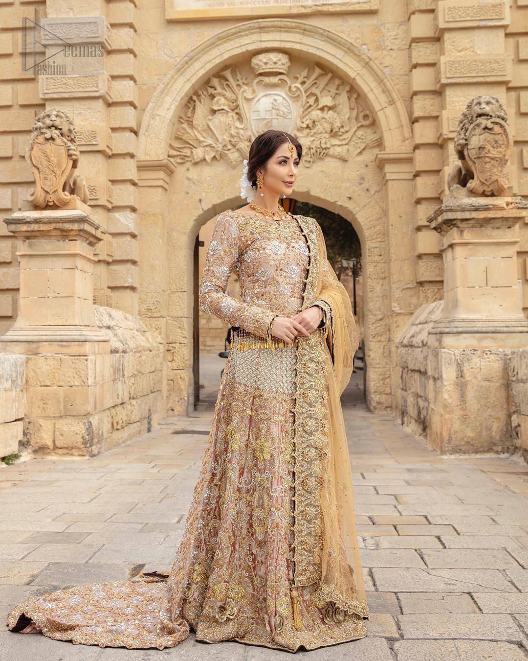 Strike a breathtakingly elegant pose in this wedding dress, designed with a beautiful blouse and a dramatic train. This artisan piece includes intricate hand-embellishment. This highly skilled technique involves hand needle work to add beads, kora, dabka, tilla and sequins to the fabric, giving our garments a unique look. The blouse is also enhanced with tassels on the hemline and back is adorned with horse shie neckline. Zardozi work is done in the shades of golden and silver. Dupatta is decorated with sequins spray on the canvas and finished with embroidered border on four sides which makes this outfit more beautiful.