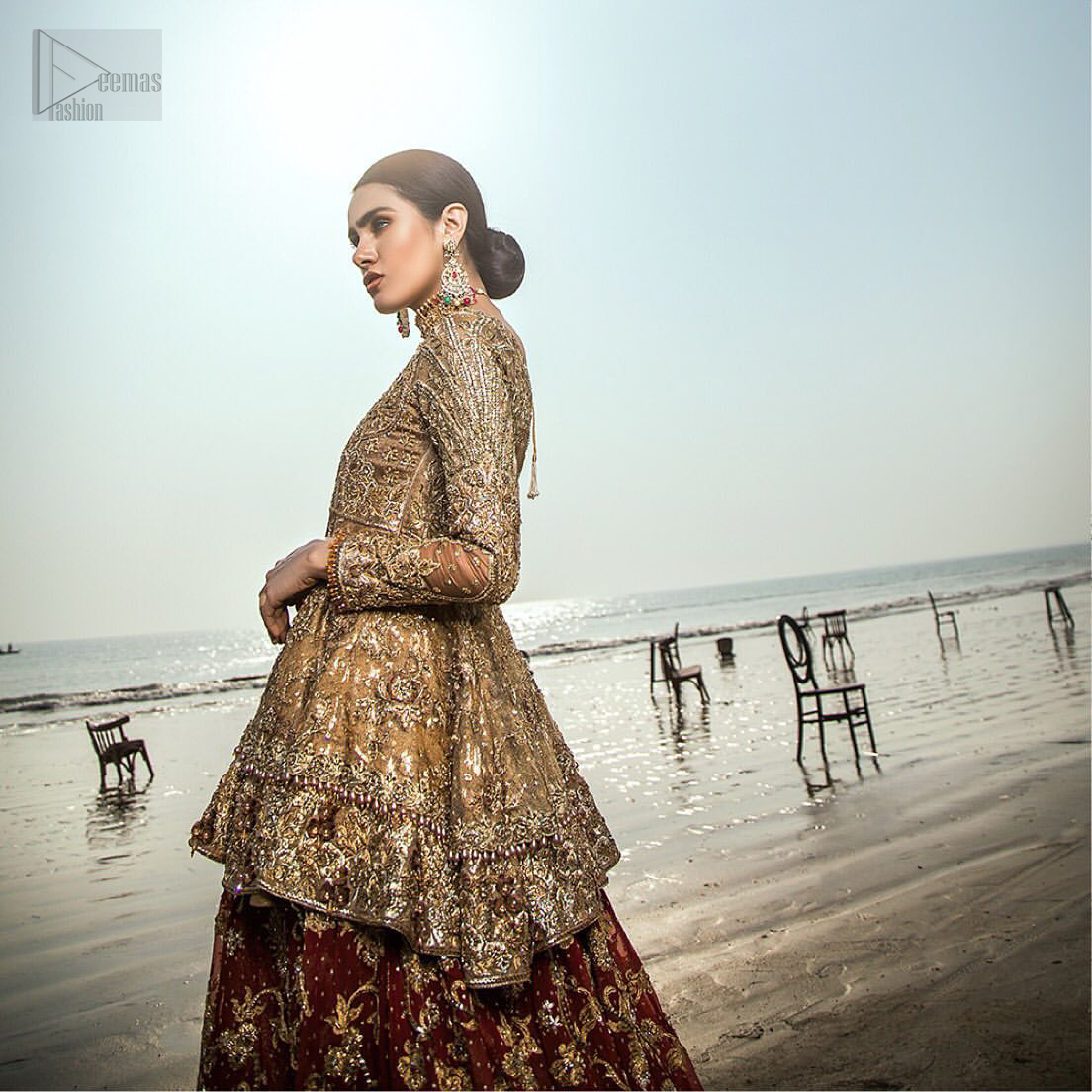 This wedding season, create a blissful aura with the treasure of love and elegance. An artistic vision of classic style and luxurious detailing infused with a bohemian spirit, transpire into a truly romantic and iconic bridal for your big day. The golden double layered peplum is heavily laden with zardozi and the perfect blend of traditional flamboyance and modern elegance in design. Pair it up with maroon lehenga enhanced with golden zardozi work. To complete the look, go with teel dupatta scattered with sequins all over the ground and heavily embellished borders to give it a perfect maharani look.