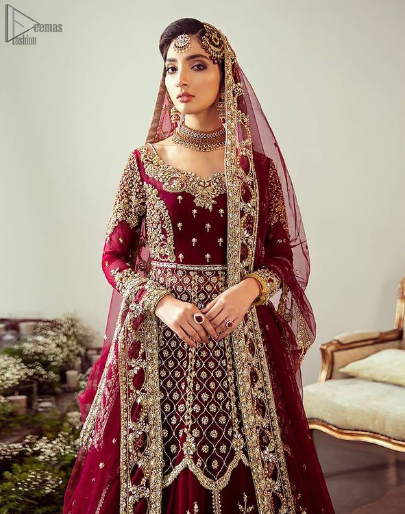 Maroon Floor Length Pakistani Reception Wear Pishwas with Bridal Dupatta and Churidar Pajama. A sensational affair so timeless and magnificent, beautifully crafted with light golden zardozi work. Craftmanship and skills you've never witnessed before. It is paired with an ethereal bridal dupatta focusing on kora and dabka handwork borders on all four sides, finishing with scattered tiny floral motifs on the ground.