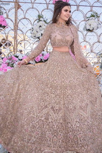 Picturing your bridal in a tea rose colour? This subtleness laden with ornamental embellishments and embroidery creates such a fairytale touch to your wedding. The boat-shaped blouse is emphasized with light golden zardozi work and finished with dangling pearls. Paired up with matching lehenga creates an unusual charisma wholeheartedly. Featuring beautiful handwork and a delicate arrangement of hand-embellished floral patterns with zardozi work along the length of lehenga. Refined craftsmanship is at its best with a hand embellished dupatta. The dupatta incorporates beautifully designed borders on all four sides, focusing on the heavily embellished pallu borders to give it a perfect maharani look.