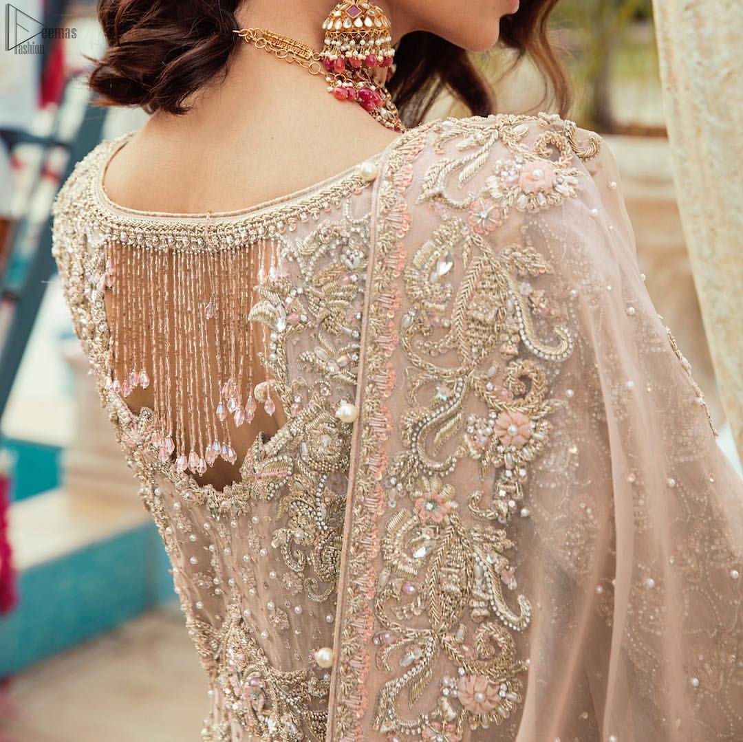 Bringing traditional charm to your big day with intricately silver and light golden embellished neckline and thick worked lines all around the flare on Tea rose canvas of Pishwas. Tea Rose pure Organza Pishwas adorned with heavy embroidery all over it. The nikah Pishwas has beautiful danglings on the back of the neckline and it comes with a pure banarsi jamawar lehenga having large thick borders on the hemline. This nikah wear tea rose Pishwas, pure banarsi jamawar lehenga comes with pure organza embroidered border dupatta.