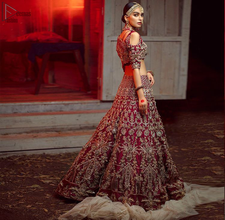 Maroon Pakistani bridal wear half blouse and lehenga comes with dupatta. Deep red half blouse choli along with same colour Lehenga of Organza Fabric with Golden-Ivory Embroidery is Everything. For a Bride planning, some exceptional outfit here comes the fully embellished, geometrical shapes having half sleeves for her Reception. The V-Neckline unifies the whole outfit with fully sprayed Tilla, Dabka work with floral motifs on Blouse Choli, Lehenga and Net Dupatta of Organza Fabric. The Lehenga has finished edges with full flare and fixed waist belt with a side zip closure along with dupatta of same deep red colour with heavy full embellished four borders.